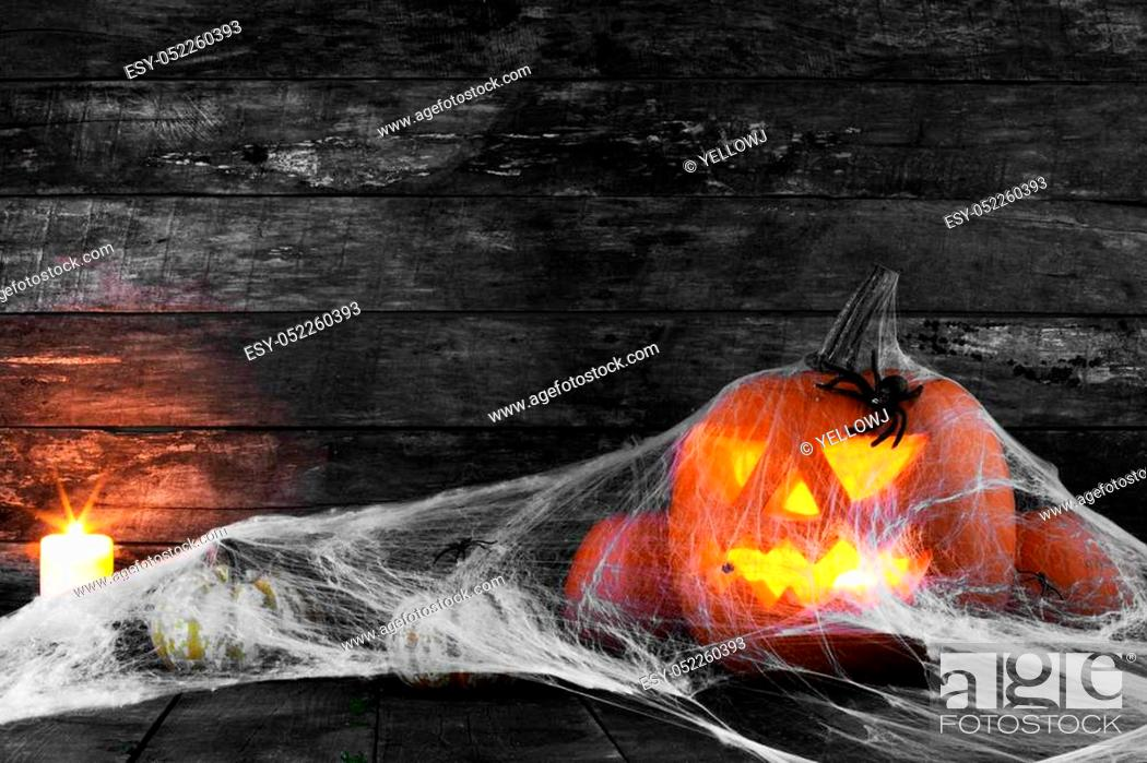 Stock Photo: Jack O Lantern Halloween pumpkin, spiders on web and burning candles.