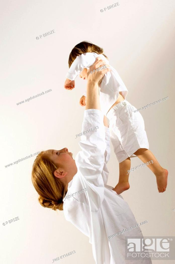 Stock Photo: Side profile of a young woman lifting up her son.