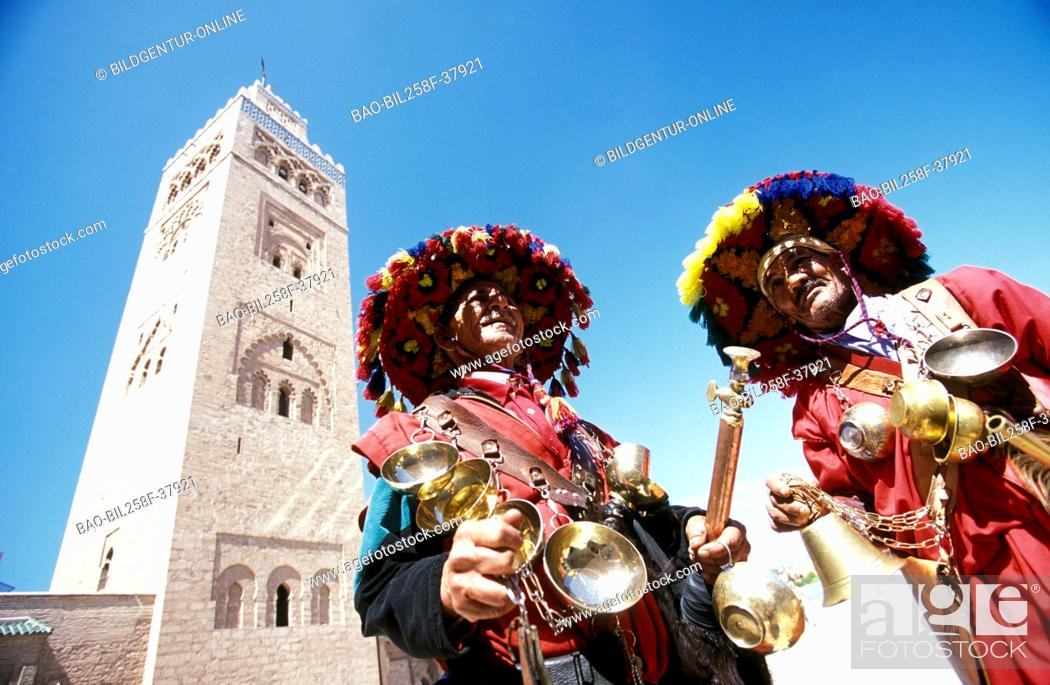 Stock Photo: Traditional water carriers and bateleur eagles before the Koutoubia mosque in the Djemma el Fna place in the Old Town of Marrakesh in Morocco in North Africa.