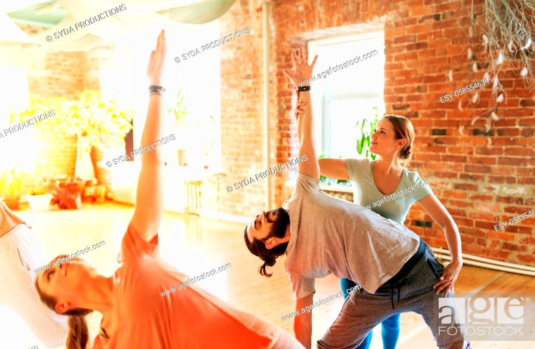 Stock Photo: group of people doing yoga exercises at studio.