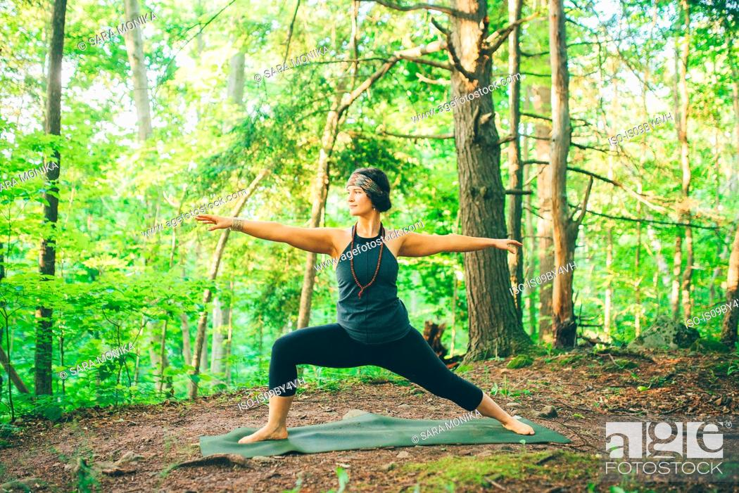Stock Photo: Woman doing warrior pose in forest.