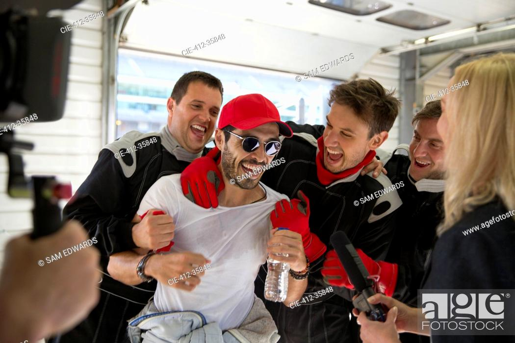 Imagen: Formula one driver and team celebrating victory in repair garage.