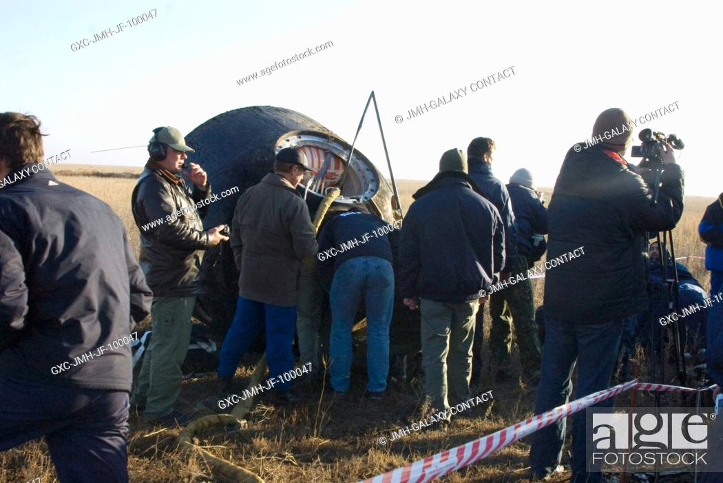 Stock Photo: Russian search and recovery crewmembers examine the Soyuz TMA-12 capsule after it landed on the steppes of Kazakhstan on Oct.