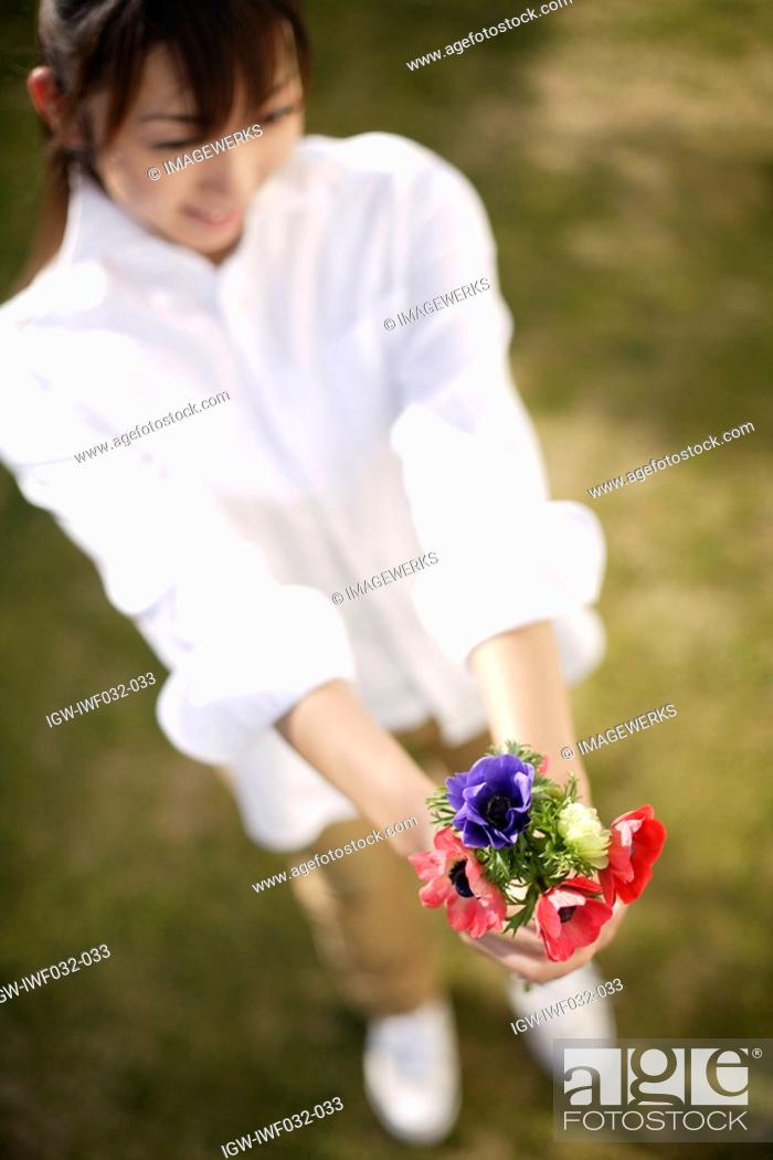Stock Photo: View of a woman holding flowers.