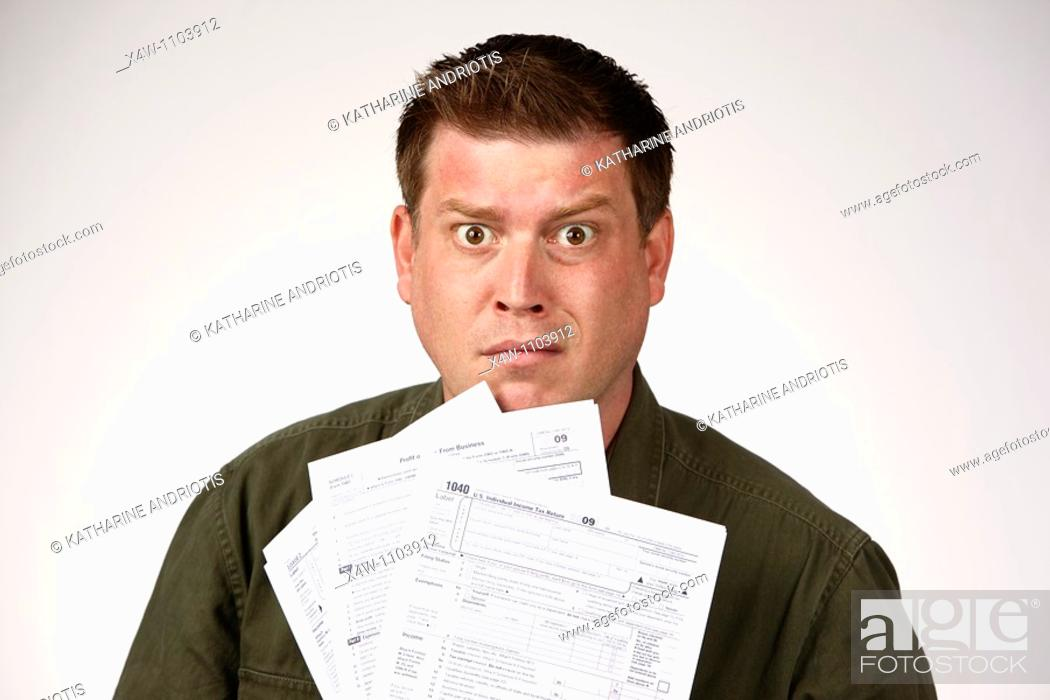 Stock Photo: Man holding United States 1040 tax forms and feeling anxious about his taxes.