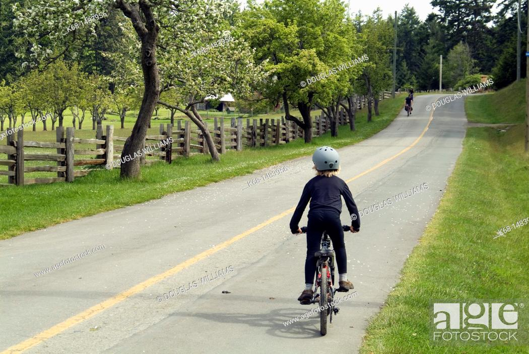 Stock Photo: a boy bicycles on Saltspring Island, BC, Canada.