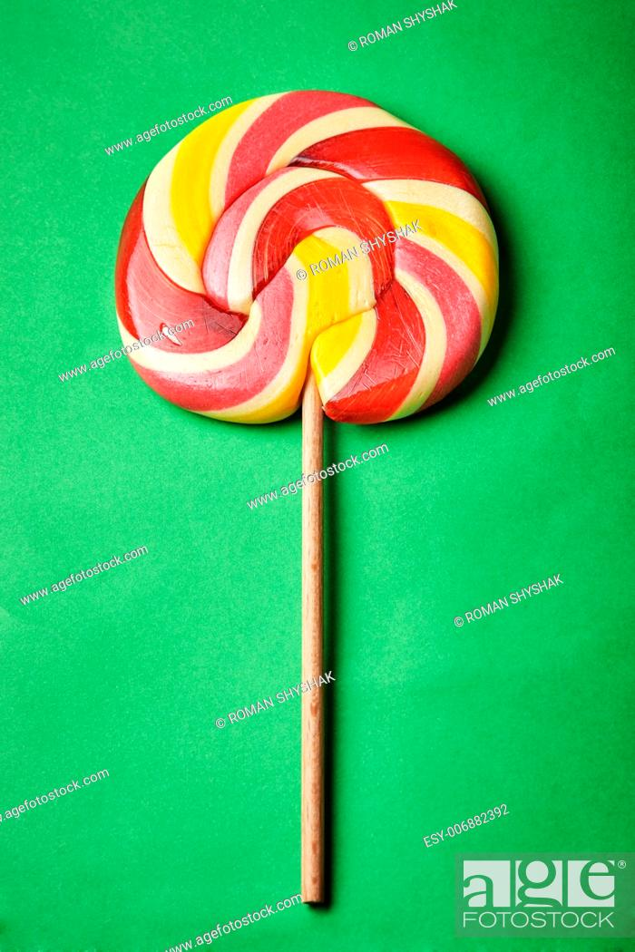 Stock Photo: Red-Yellow Lollipop on green background.