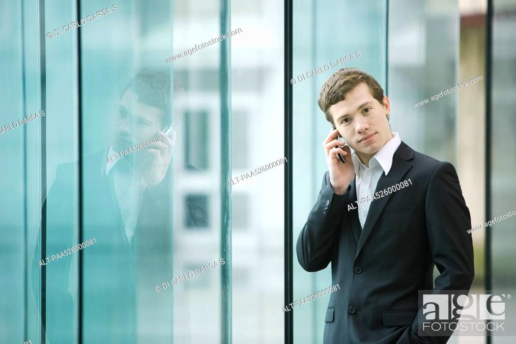 Stock Photo: Businessman standing by glass wall talking on cell phone.