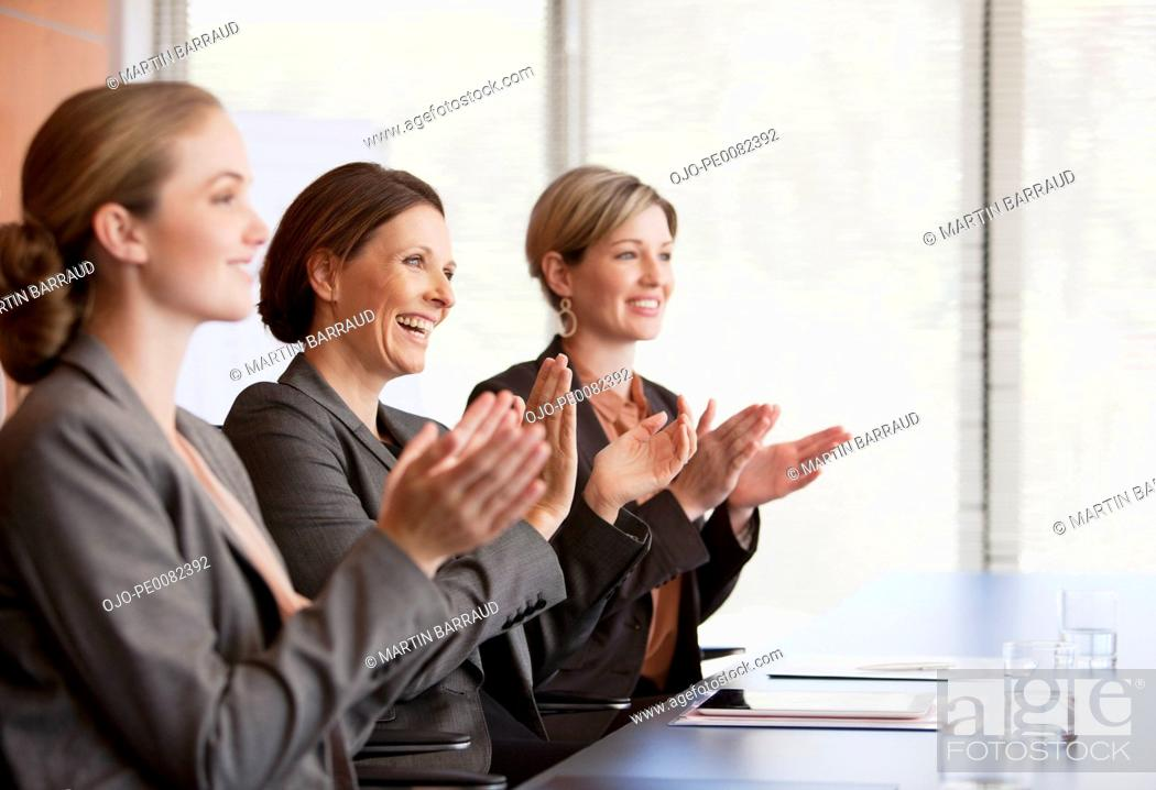 Stock Photo: Businesswomen clapping in conference room.
