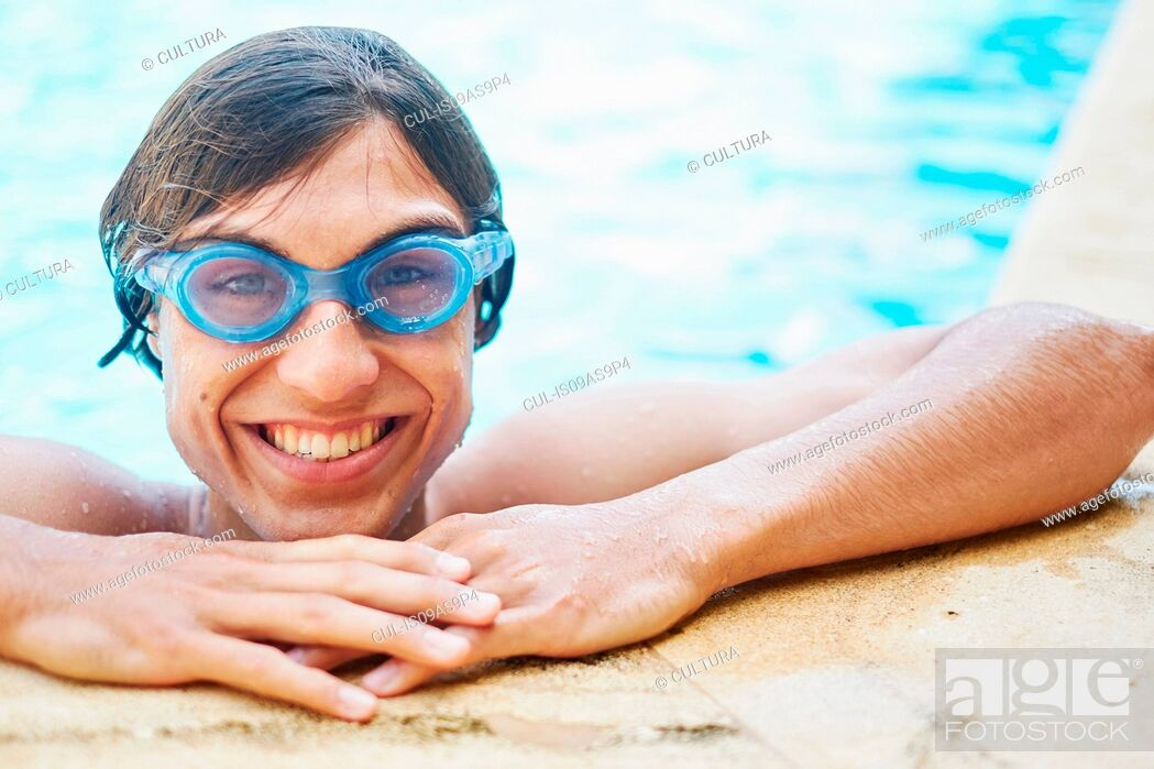 Imagen: Portrait of young man wearing goggles in swimming pool.