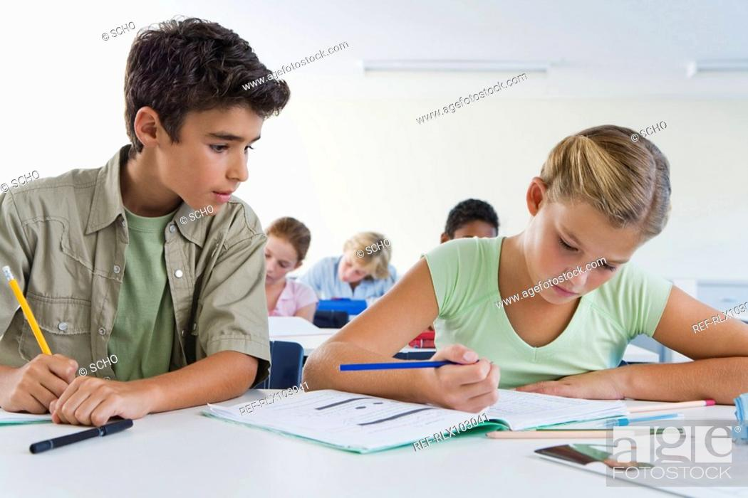 Stock Photo: Boy and girl 10-13 in classroom, boy copying girls work, cheating.