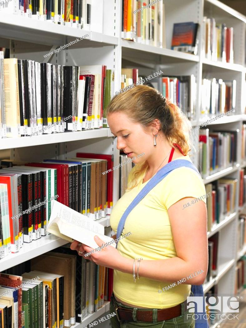 Stock Photo: Young woman reading book in library.
