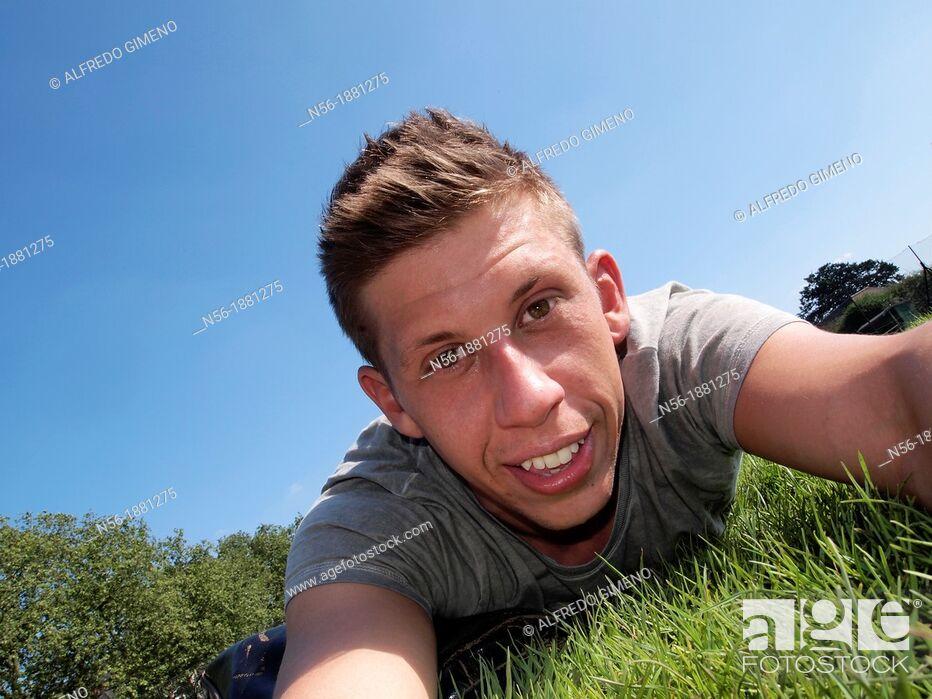 Stock Photo: England, London, Portrait of man lying on grass.
