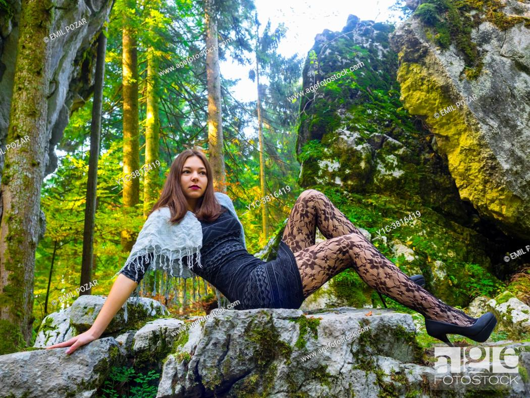Stock Photo: Young woman in nature reclining on big boulder rock looking away.