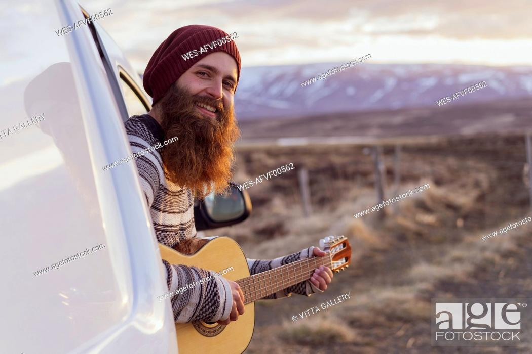 Stock Photo: Iceland, young man sitting in van and playing guitar.