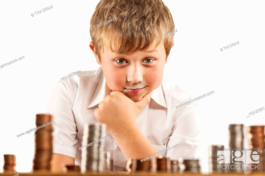 Stock Photo: A young boy of 10 counts his money and stacks it up.