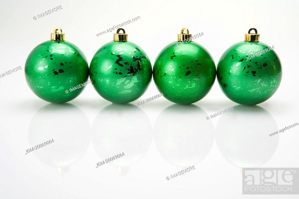 Stock Photo: A row of green Christmas baubles.