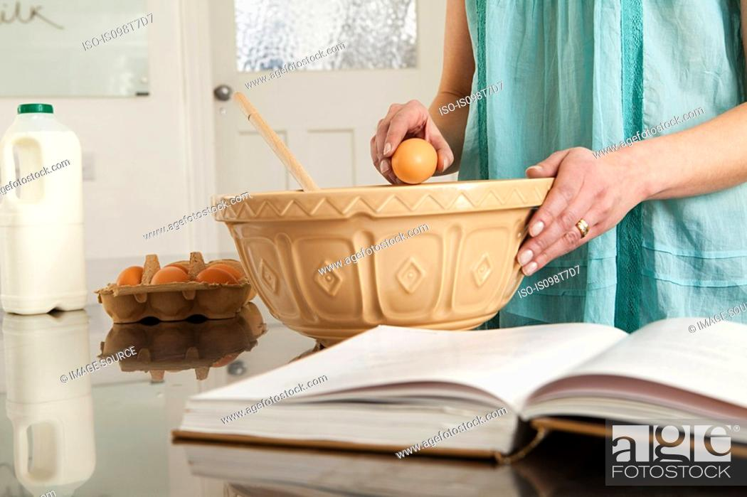 Stock Photo: Woman breaking egg into bowl.