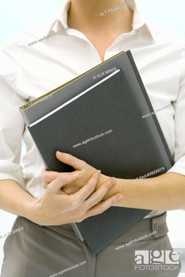 Stock Photo: Female professional holding folders, cropped view.