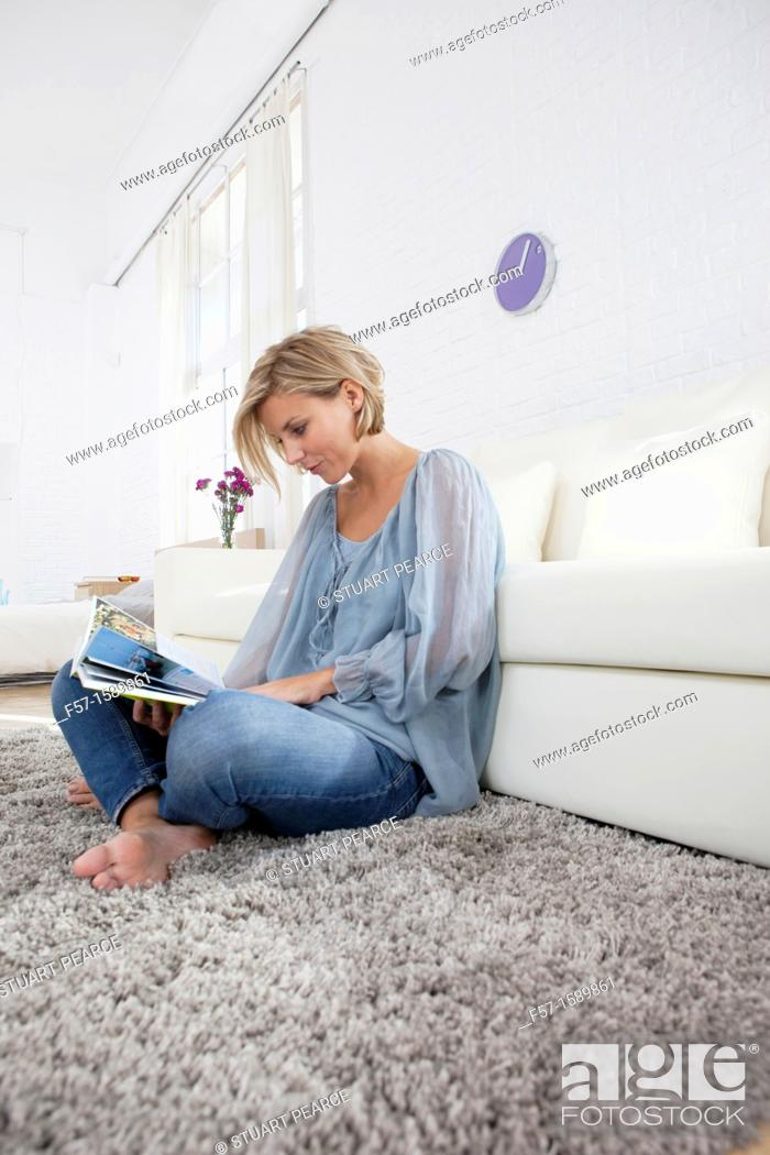 Stock Photo: Young woman reading in her living room.
