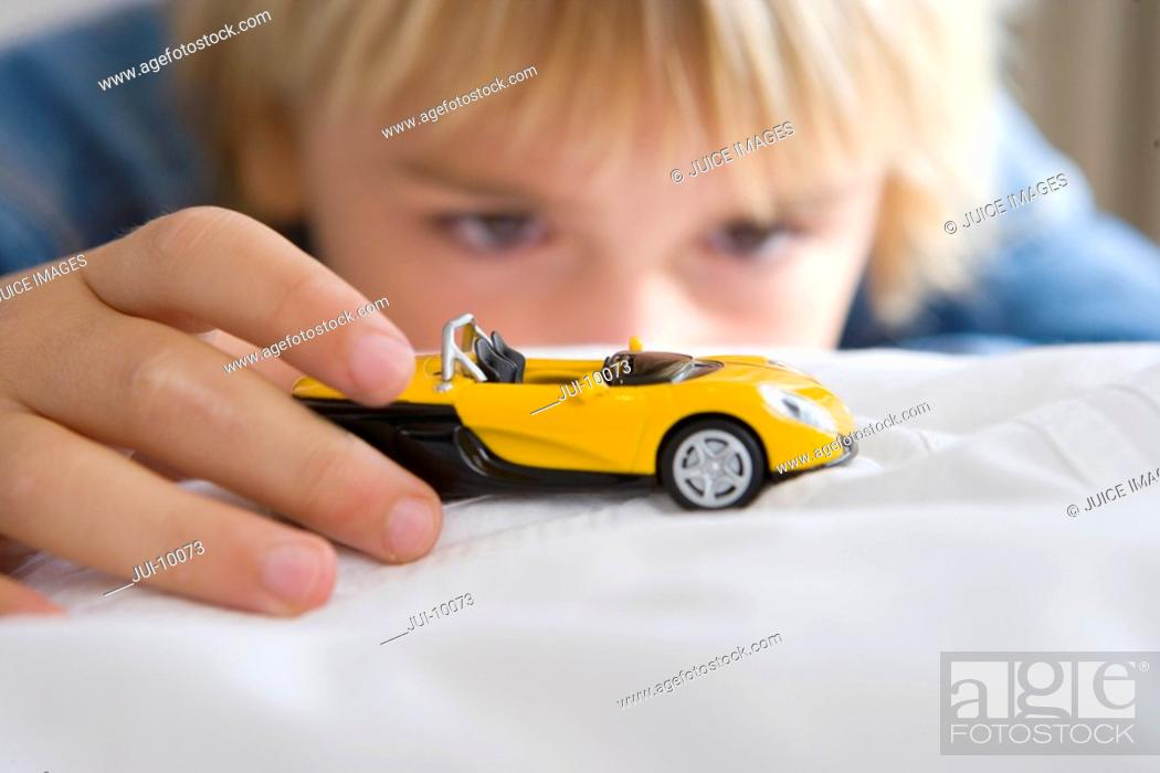Stock Photo: Boy 6-8 playing with toy car differential focus.