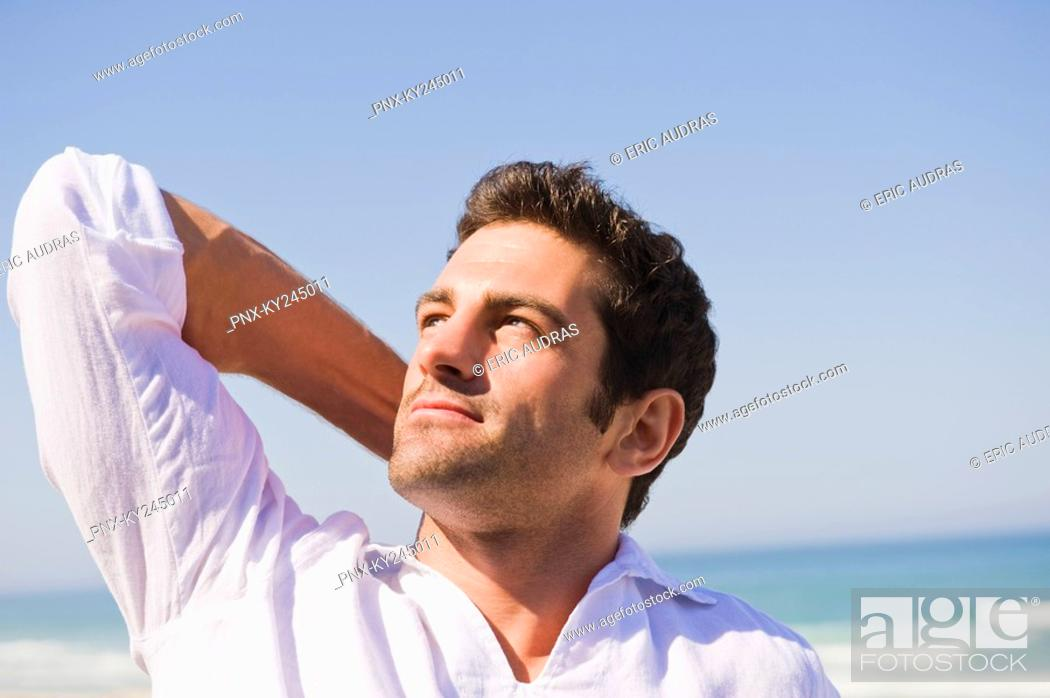 Stock Photo: Man looking up on the beach.