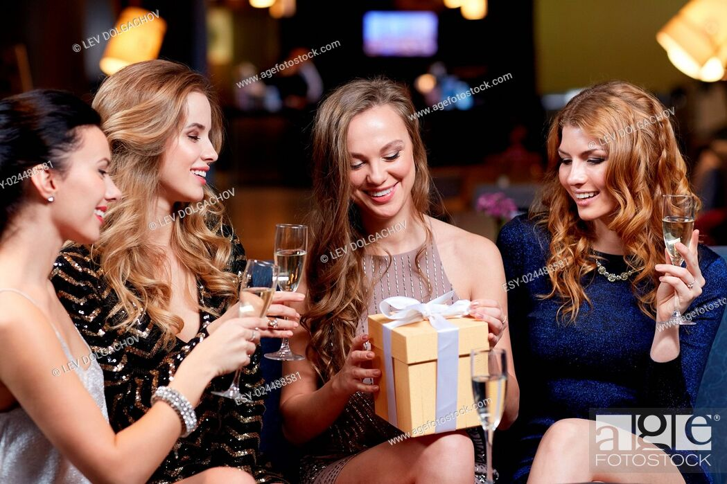 Stock Photo: celebration, friends, bachelorette party, birthday and holidays concept - happy women with champagne glasses and gift box at night club.