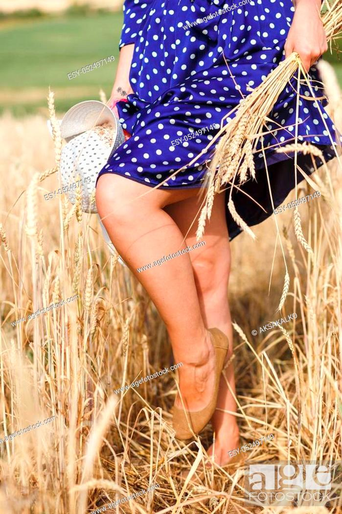 Stock Photo: legs of young beautiful brunette girl walking in the field.