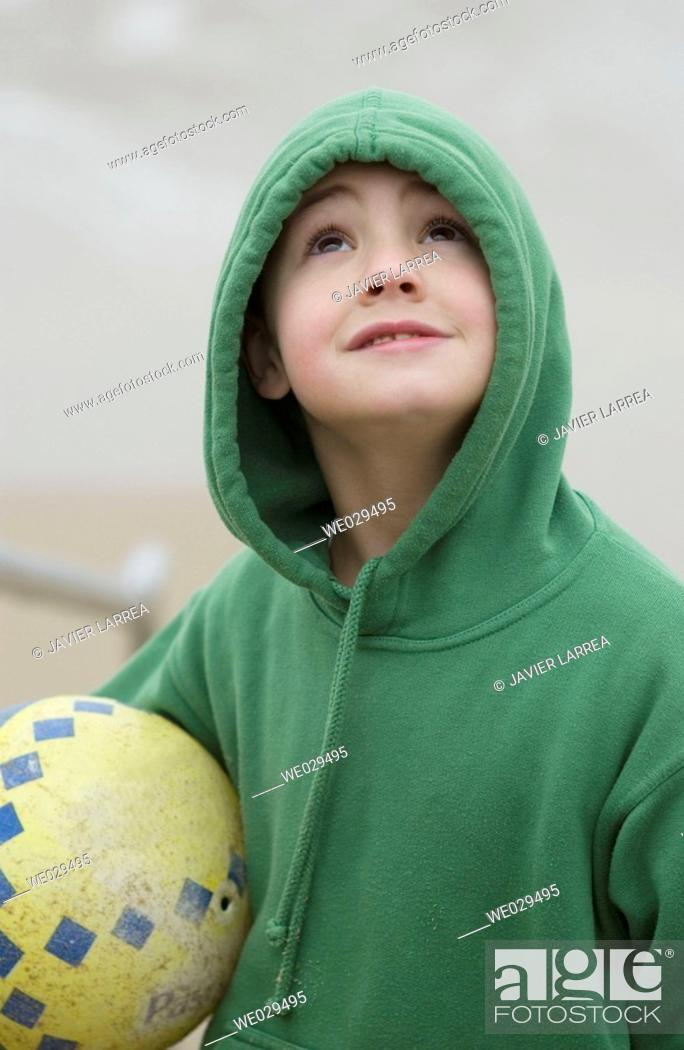 Stock Photo: Boy holding a ball at beach. Hendaye. Aquitaine, France.