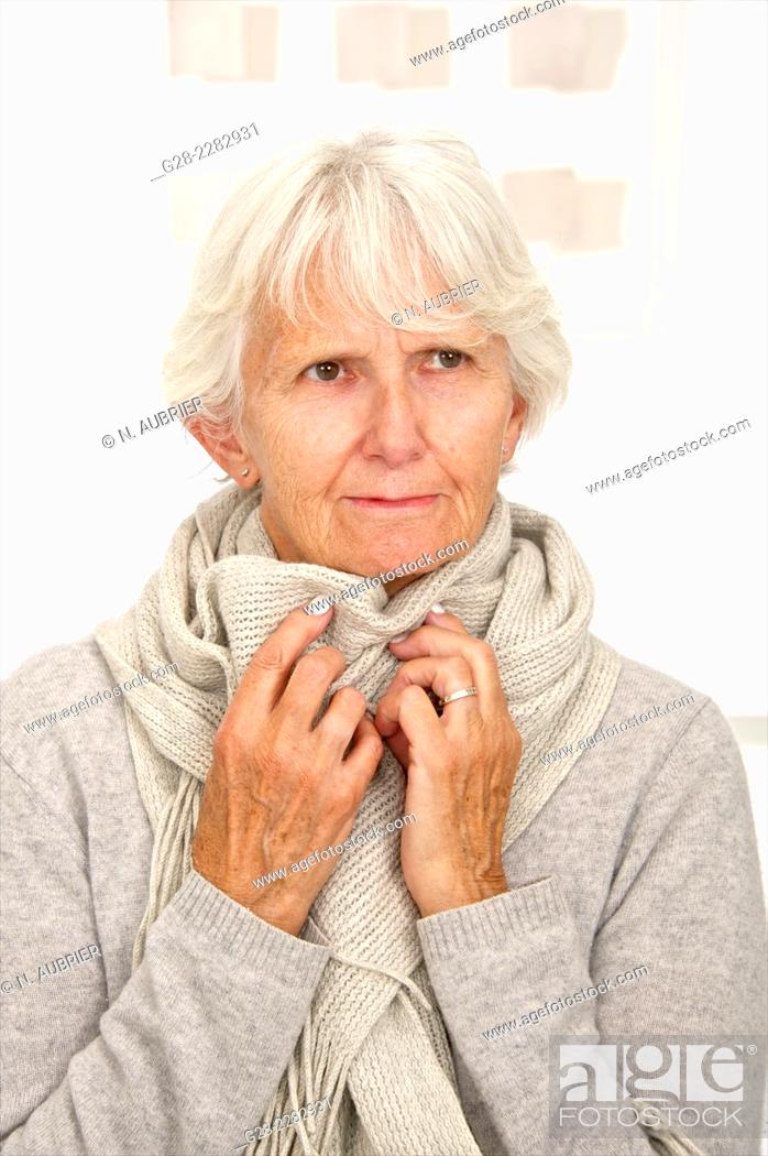 Stock Photo: Senior woman in grey feeling cold and wrapping herself in a woolen scarf.