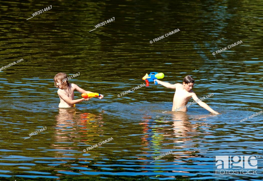 Stock Photo: Two Boys Fighting with Squirt Guns in the Lake.