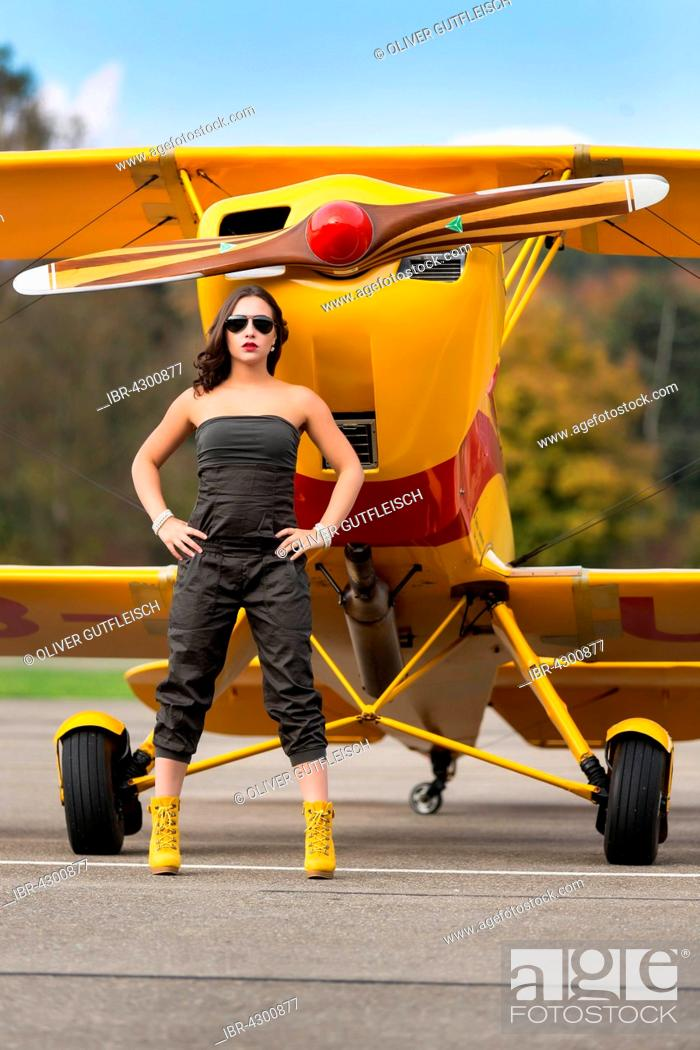 Stock Photo: Young woman with sunglasses in overall and boots posing in front of double-decker airplane, fashion, lifestyle, photo shoot.