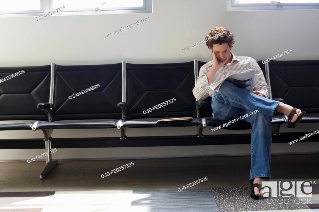 Stock Photo: Man sitting cross legged reading a newspaper.