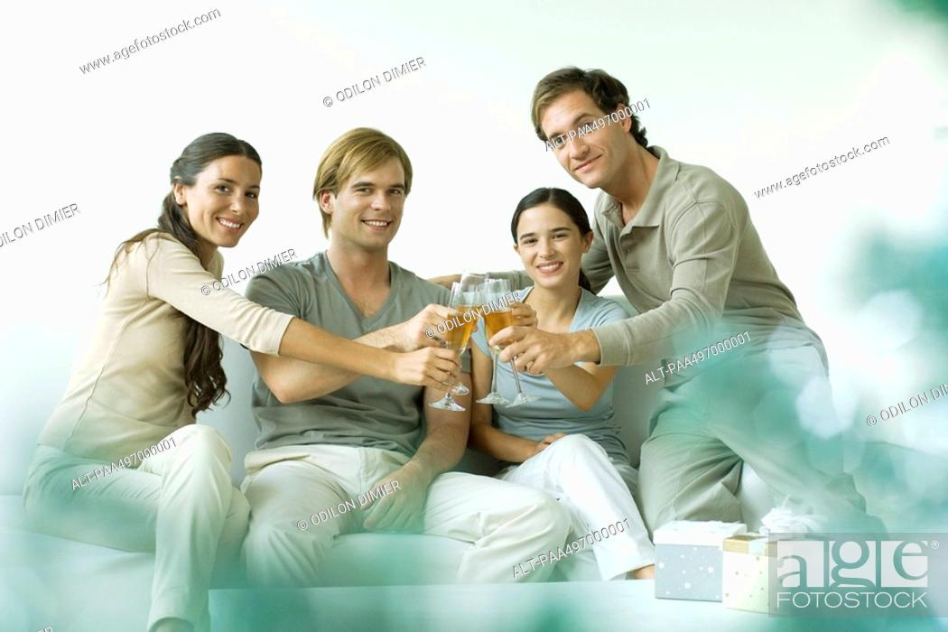 Stock Photo: Adult friends clinking champagne glasses, smiling at camera.