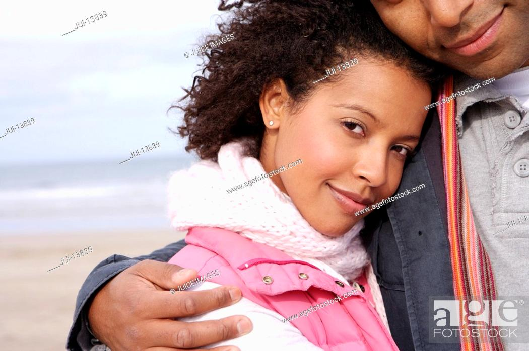 Stock Photo: Young couple embracing on beach, portrait of woman.