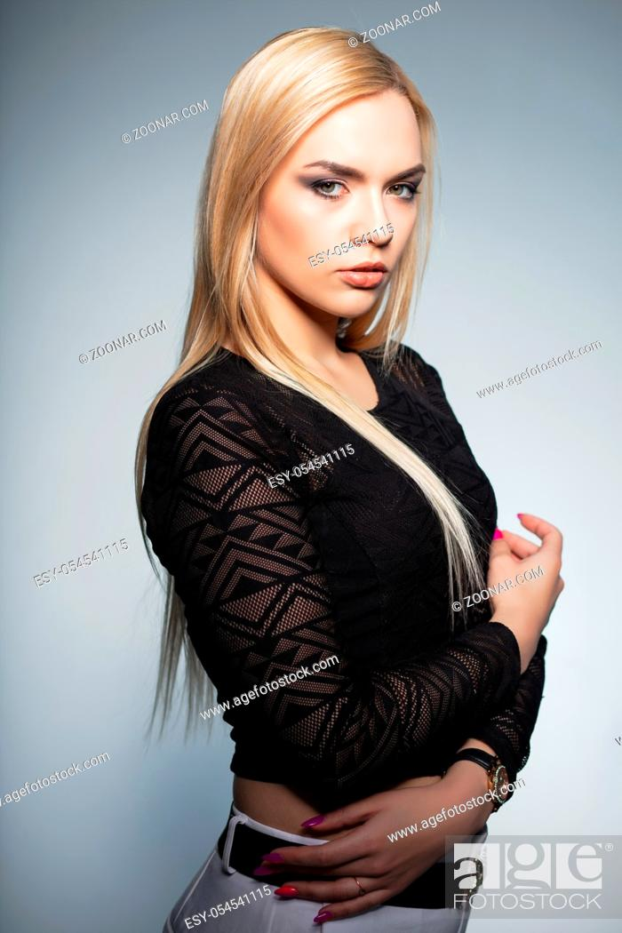 Stock Photo: Alluring blonde posing in studio on a white background, wearing a black blouse and white pants.