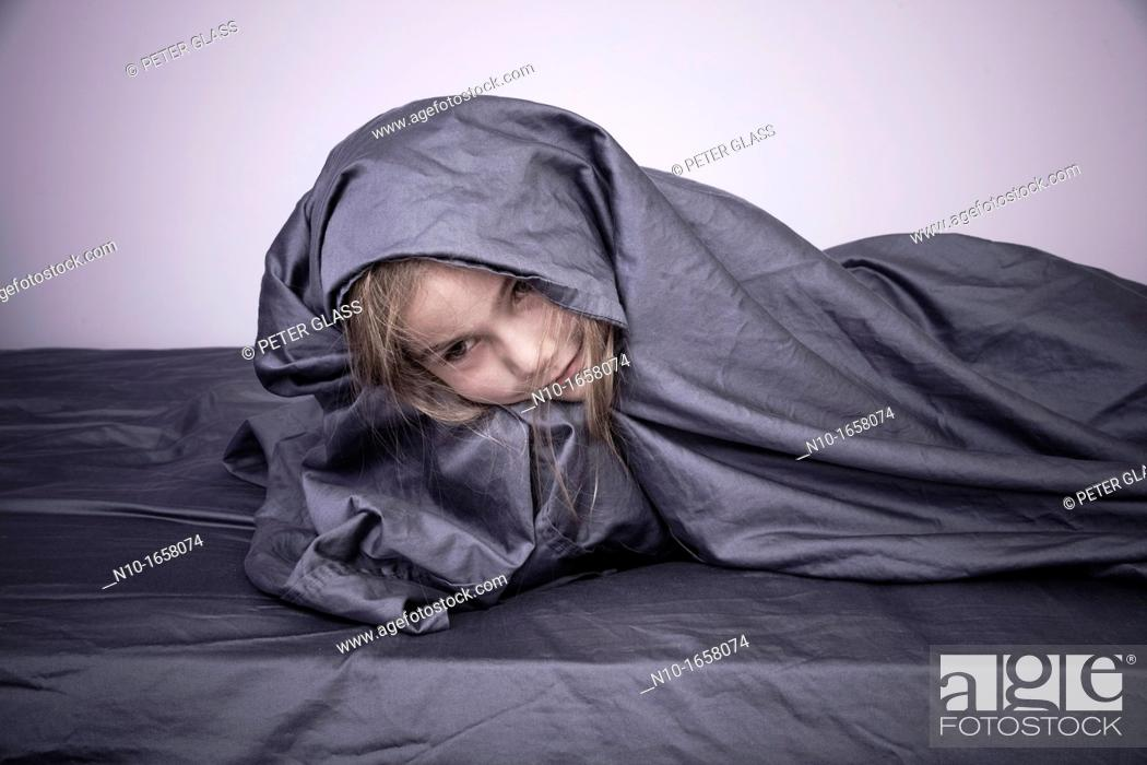 Stock Photo: Young blonde girl with the bed sheet around her.