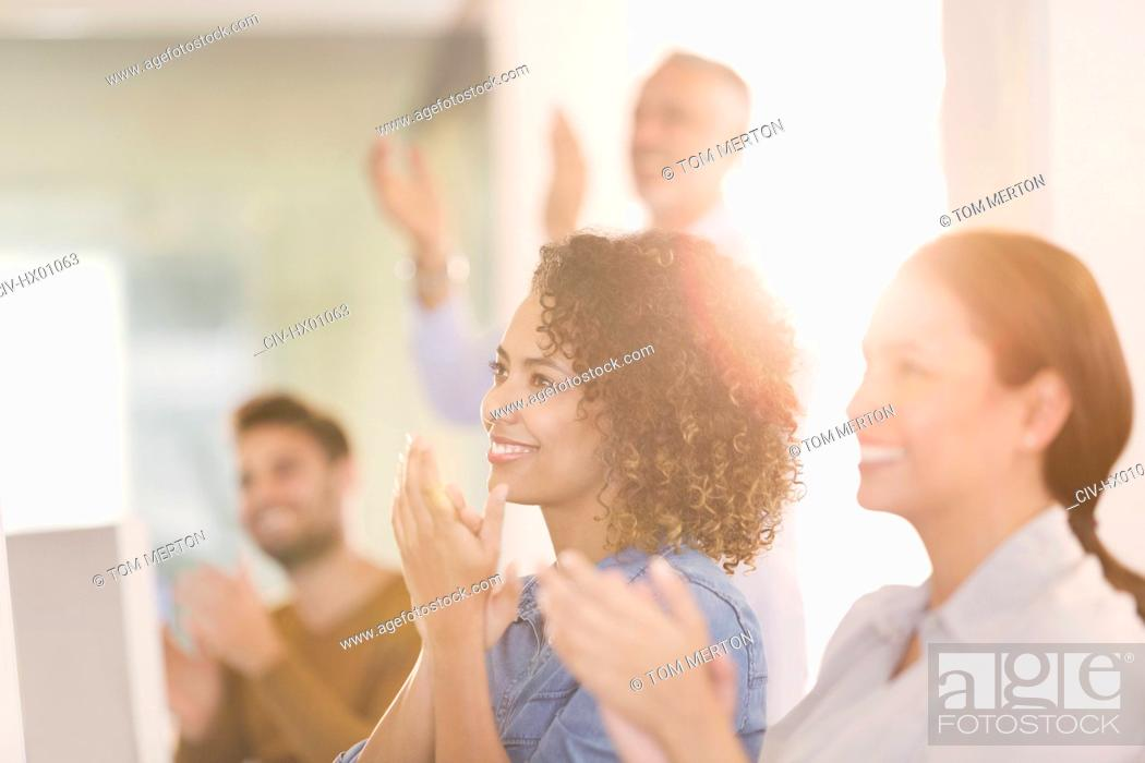 Stock Photo: Businesswomen clapping in office.