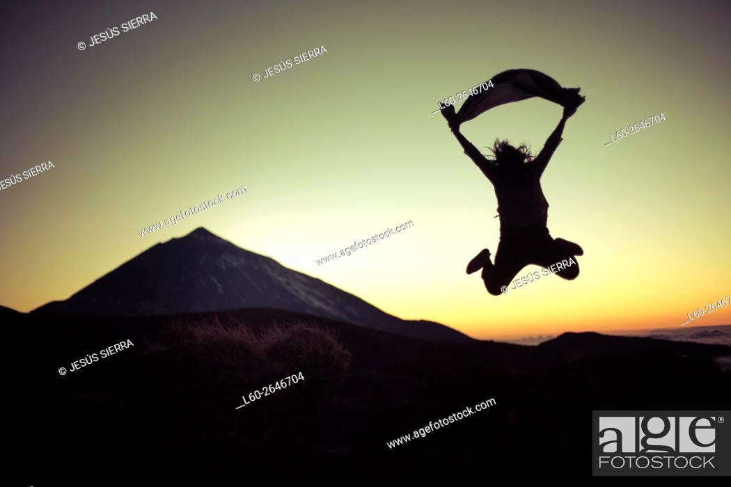 Stock Photo: Young woman jumping in Parque Nacional del Teide, Tenerife, Canary Islands, Spain.