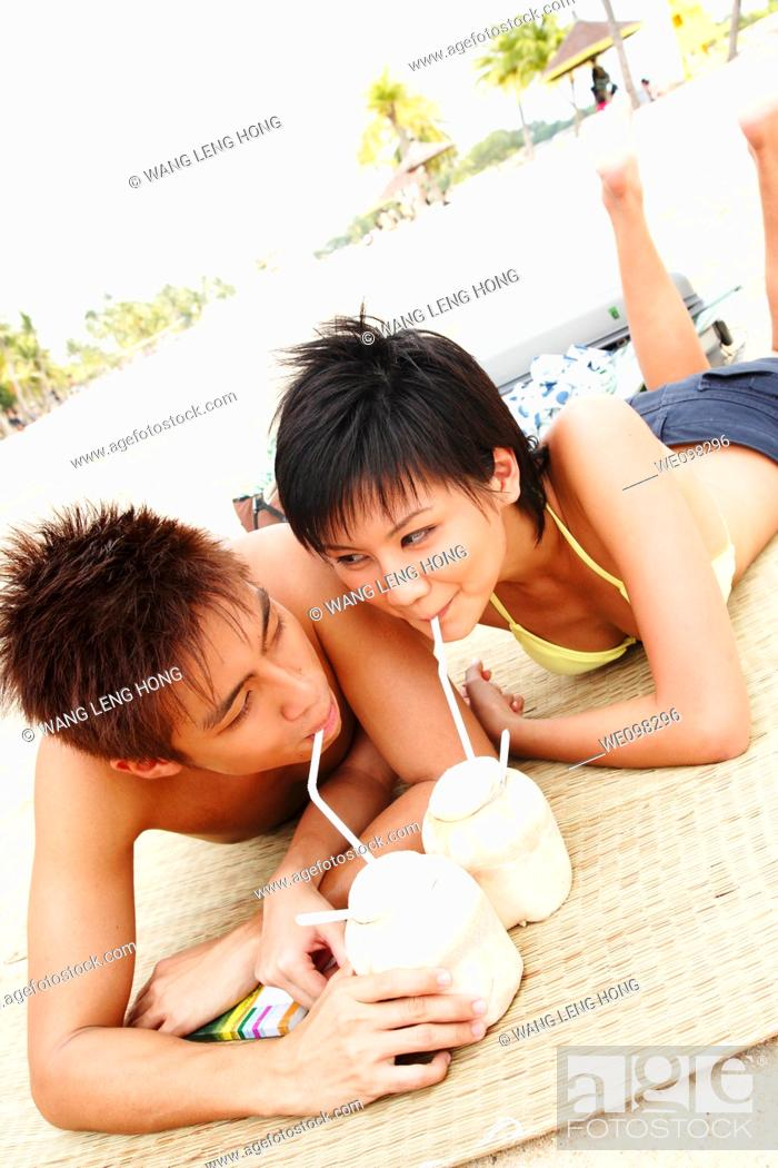 Stock Photo: young asian couple relaxing at beach.