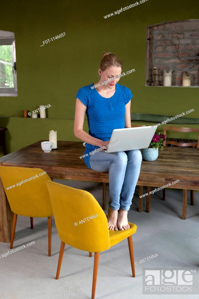 Stock Photo: A woman sitting on her dining table using a laptop.