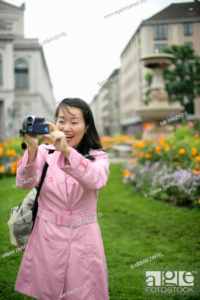 Stock Photo: Young Asian woman with a camera standing in front of a park and is laughing, selective focus.
