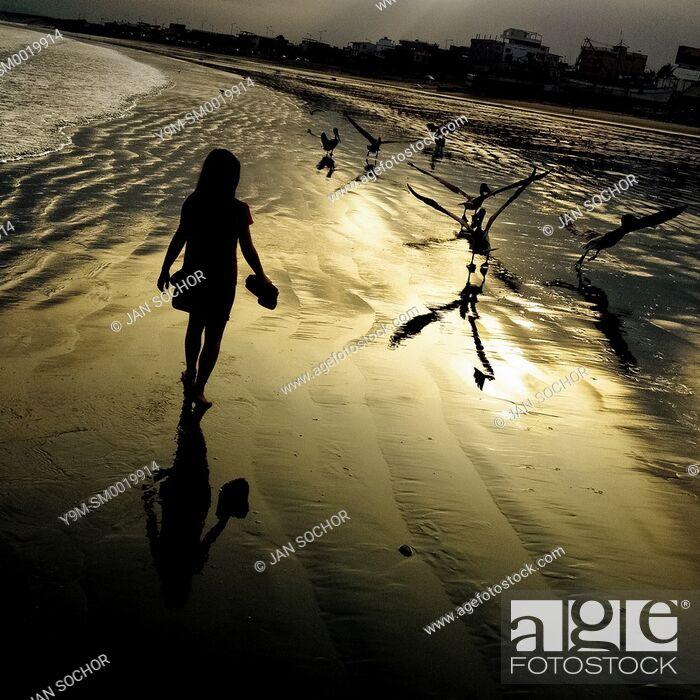 Stock Photo: A girl walks on the low-tide beach at the sunrise in Manta, Ecuador, 20 November 2014.