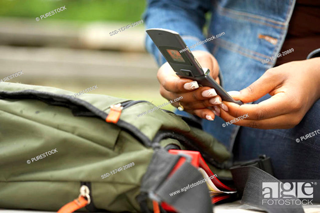 Stock Photo: Mid section view of a college student using a mobile phone.