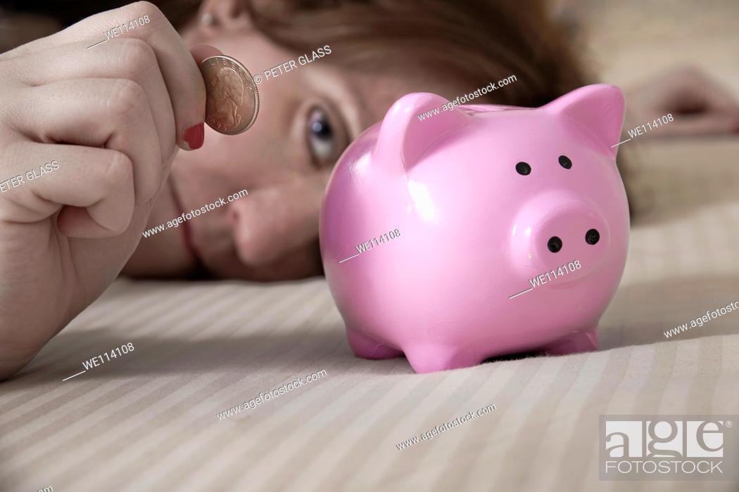 Stock Photo: Woman putting an American quarter into a piggy bank.