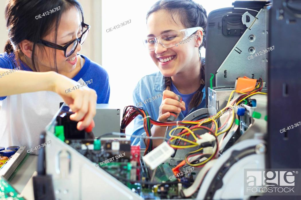 Stock Photo: Smiling girl students assembling computer in classroom.