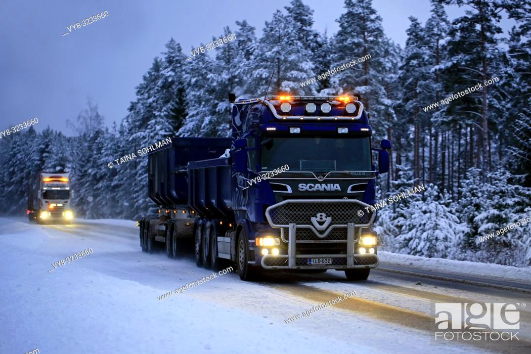 Stock Photo: Salo, Finland - January 25, 2019: Two trucks, Scania V8 for limestone haul in the front at speed with beautiful lights lighting up the dark rural road.