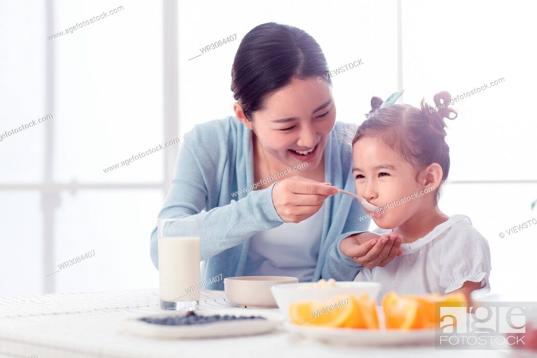 Stock Photo: Mother is feeding the girl.