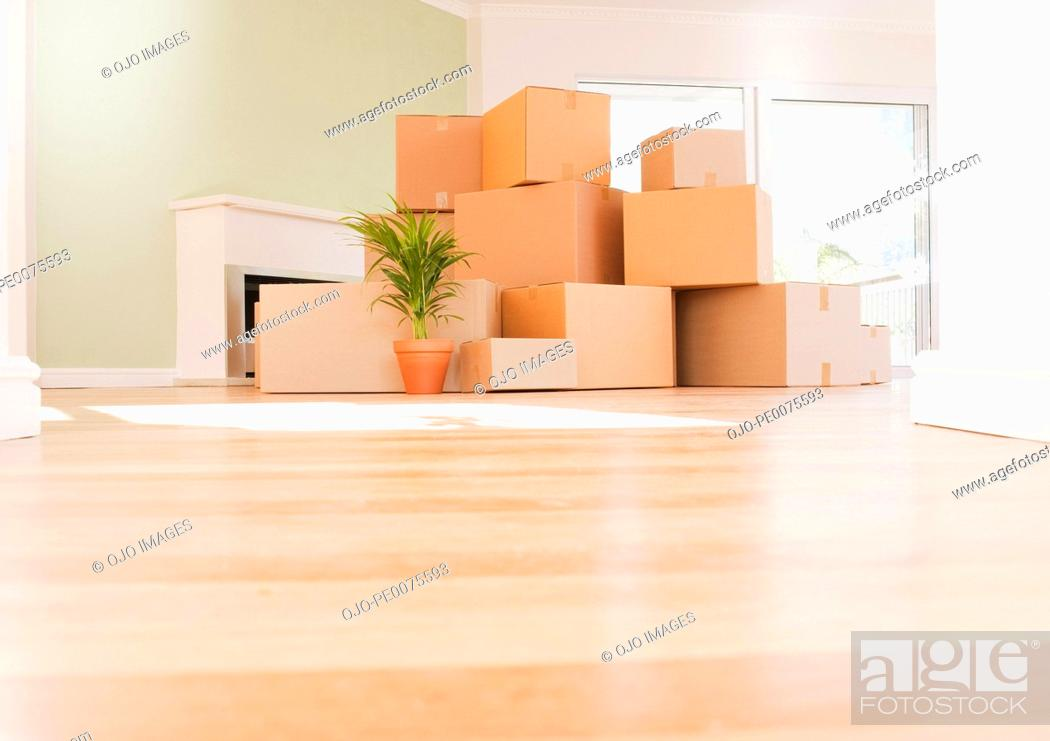 Stock Photo: Boxes stacked on wooden floor of new house.