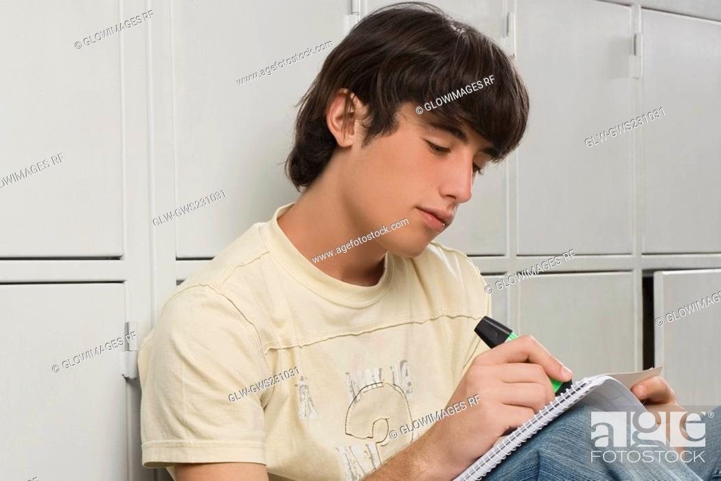 Stock Photo: Close-up of a young man writing with a highlighter.